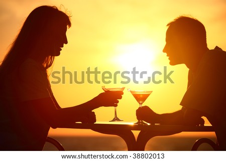 man and woman clink glasses on sunset outside and talking - stock photo