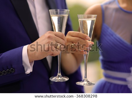 Man and woman clink glasses with champagne. Wedding or Valentine's day