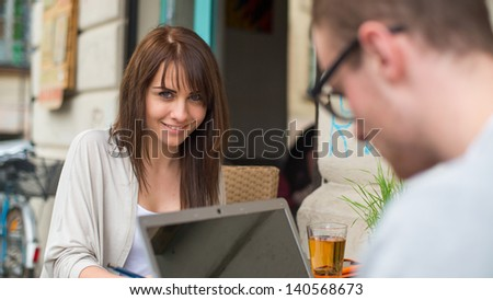 Man and woman couple in the cafe on laptop computer. They are happy.