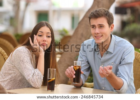 Man and woman dating in a restaurant terrace but she is boring while he telling lies with the street in the background - stock photo