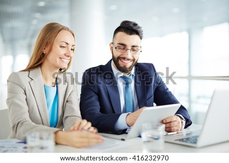 Man and woman discussing business on touchpad - stock photo