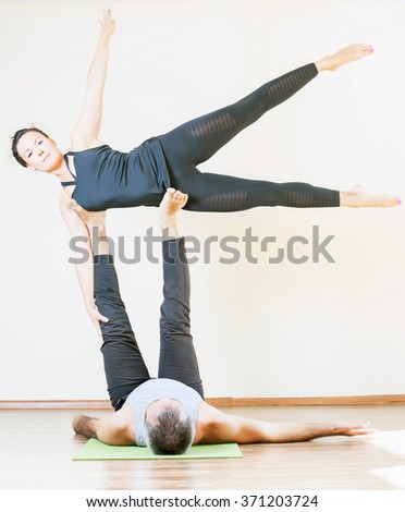 Man and woman doing acro yoga or yoga with partner indoor. Concept of couple in sport or family healthy lifestyle