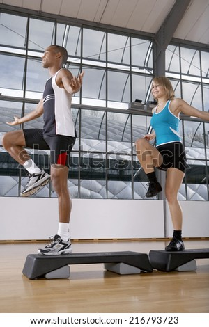 Man and woman doing step aerobics.