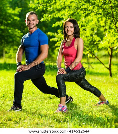 Man and woman doing stretching exercises at summer park.  Young couple exercising and stretching muscles before sport activity - outdoor in nature - stock photo
