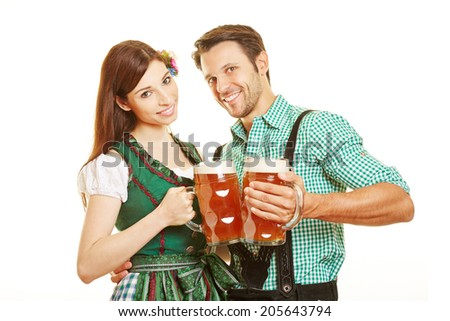 Man and woman drinking beer in Bavaria and clinking their glasses - stock photo