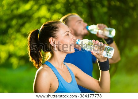 Man and woman drinking water from bottle after fitness sport exercise - stock photo