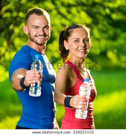 Man and woman drinking water from bottle after fitness sport exercise. Smiling couple with bottles of cold drink outdoors - stock photo
