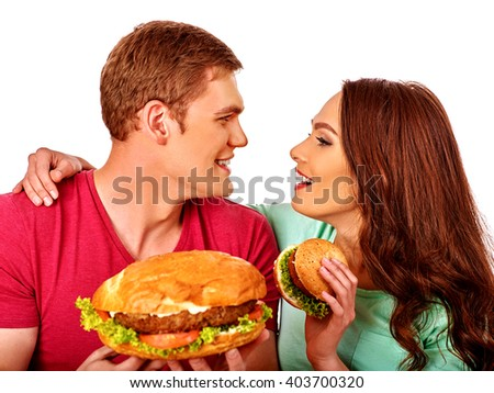 Man and woman eating hamburgers  . Fastfood concept not useful food .  Isolated.  - stock photo