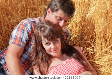 Man and woman embracing in a wheat field - stock photo