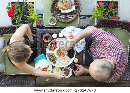 Man and woman enjoying an outdoor Turkish breakfast sitting together at a small intimate table helping themselves to a selection of food with Turkish tea, overhead view - stock photo