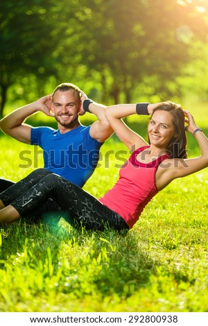 Man and woman exercising at the city park. Beautiful young multiracial couple. Sit ups fitness couple exercising outside in grass. Fit happy people working out outdoor. - stock photo