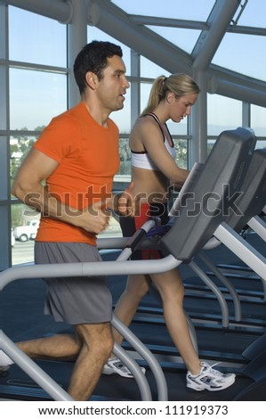 Man and woman exercising on treadmill