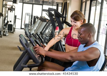 Man and woman exercising together at a fitness center on a stationary bicycle exercise machine.  Woman could be a personal fitness trainer. Focus is on the man in the foreground.