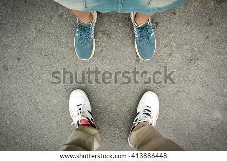 man and woman feet standing on the road - stock photo