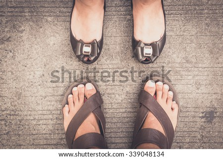 man and woman feet wearing shoes  standing on the asphalt concrete floor - stock photo