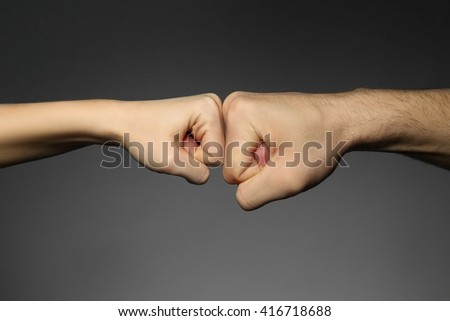 Man and woman fists on grey background
