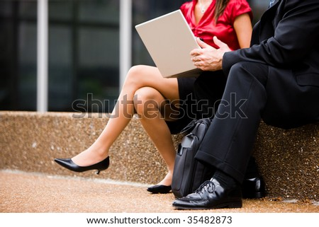 Man and woman from shoulder down sitting with a laptop
