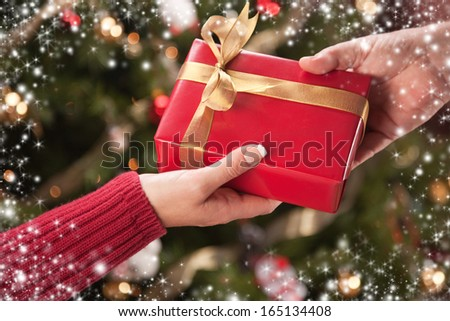 Man and Woman Gift Exchange in Front of Decorated Christmas Tree with Snow Flakes Border. - stock photo