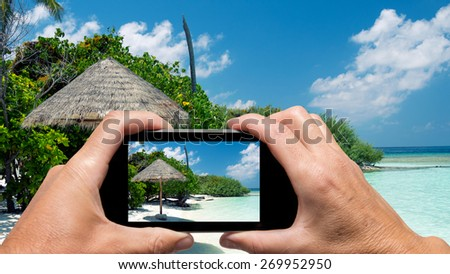 Man and woman hand capturing Maldivian Island colors with smartphone.