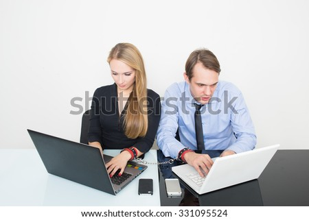 man and woman handcuffed. working in the office for notebooks - stock photo