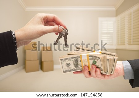 Man and Woman Handing Over Cash For House Keys Inside Empty Tan Room with Boxes. - stock photo