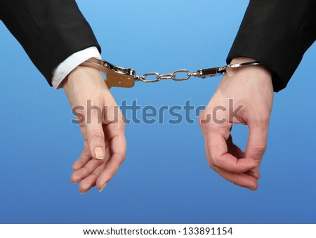 Man and woman hands and breaking handcuffs on color background - stock photo