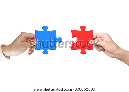 Man and woman hands assembling different color puzzle pieces, isolated on white. Teamwork concept.