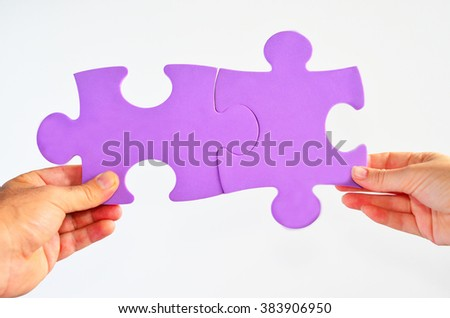 Man and woman hands holds two different jigsaw puzzle pieces connected on a white background. Relationship concept - stock photo