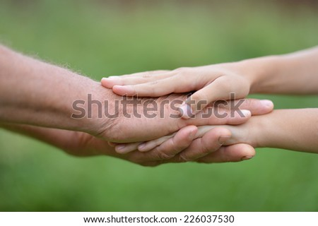 Man and woman hands together over natural background - stock photo