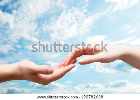 Man and woman hands touch in gentle, soft way on blue sunny sky. Concepts of connection, hope, faith, help, love. - stock photo