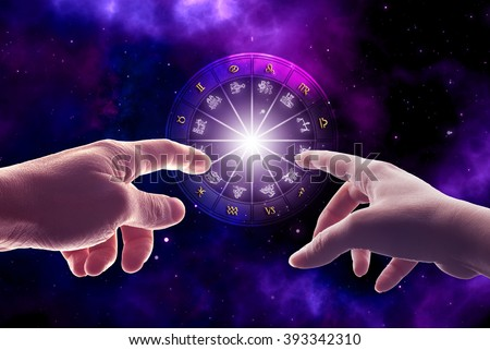 man and woman hands touching an astrology chart with all zodiac signs - stock photo
