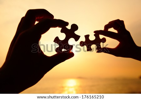 Man and woman hands trying to connect puzzle pieces  - stock photo