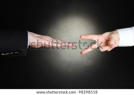 man and woman hands with thumbs up ok signal on black background. Stone, Paper, Scissors - stock photo