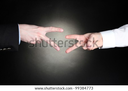 man and woman hands with thumbs up ok signal on black background. Stone, Paper, Scissors