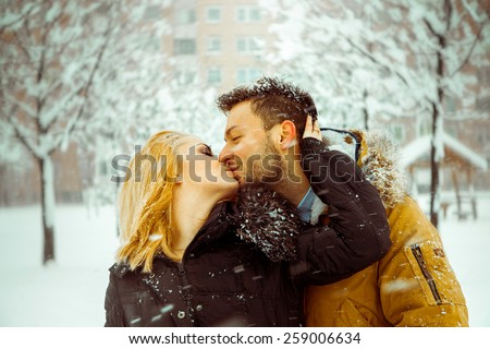 Man and woman happily kissing on the street in the snow. Horizontal color image - stock photo