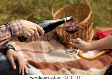 Man and woman having a picnic. He pours red wine in her glass. Couple sitting on the plaid. Man pours wine from a bottle. In her hand a glass of wine. Love story. - stock photo