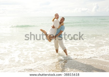 Man and woman having fun at the beach - stock photo