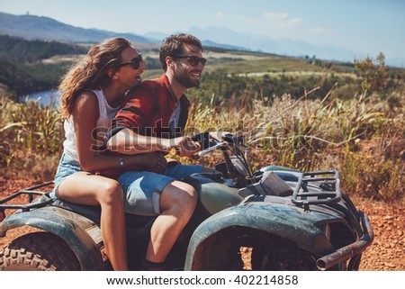 Man and woman having fun on an off road adventure. Couple riding on a quad bike in countryside on a summer day. - stock photo