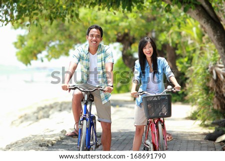 man and woman having fun outdoor riding bicycle together and smiling to the camera - stock photo