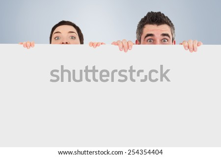 Man and woman hiding behind a white board with room for copy space against grey vignette - stock photo