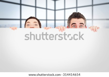Man and woman hiding behind a white board with room for copy space against room with large windows showing city - stock photo