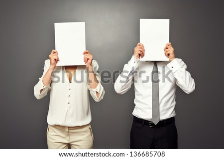 man and woman hiding their faces behind white paper - stock photo