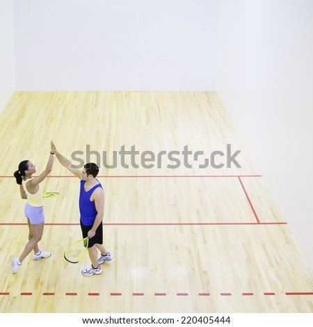 Man and woman high fiving on Squash court - stock photo