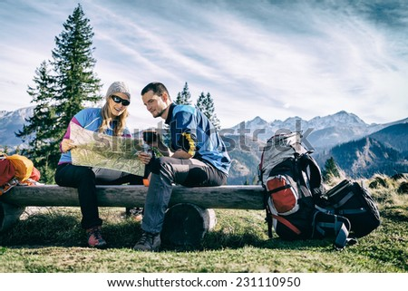 Man and woman hikers hiking in mountains. Young couple camping, looking at map and planning trip or get lost. Getting rest and drinking coffee or tea, navigation and looking for direction - stock photo