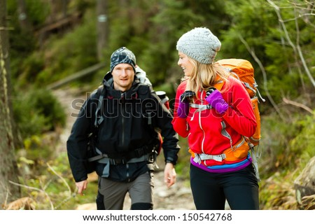 Man and woman hikers trekking in mountains. Young couple walking with backpacks in forest, Tatras in Poland. - stock photo