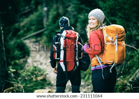 Man and woman hikers trekking in mountains. Young couple walking with backpacks in forest, Tatras in Poland. Old vintage photo style. - stock photo