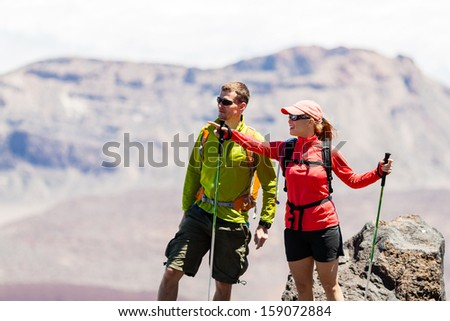 Man and woman hikers trekking in summer mountains. Young couple on rocky mountain range looking at beautiful view. Hiking on volcano mountain, Tenerife Canary Islands - stock photo