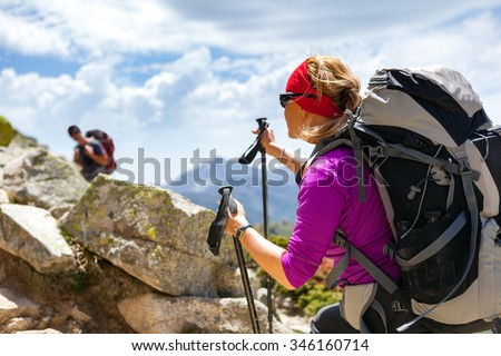 Man and woman hikers trekking in summer mountains. Young couple on rocky mountain range looking at beautiful inspirational landscape view. - stock photo