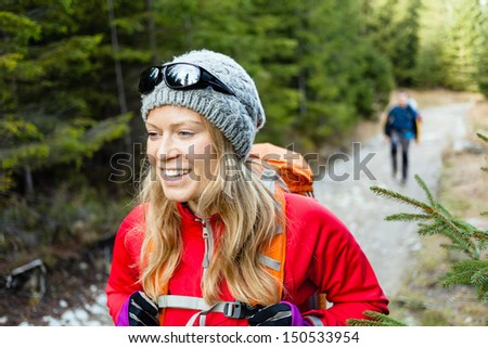 Man and woman hikers trekking on trail in mountains. Young couple walking on dirt road in forest. Holidays in Tatras, Poland. - stock photo