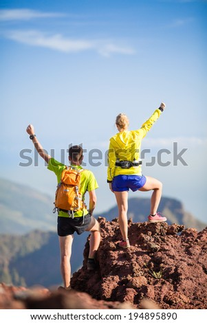 Man and woman hikers trekking or trail running in summer mountains. Young couple on rocky mountain range looking at beautiful view. Arms outstretched, success on climbing rocky hill over blue sky - stock photo